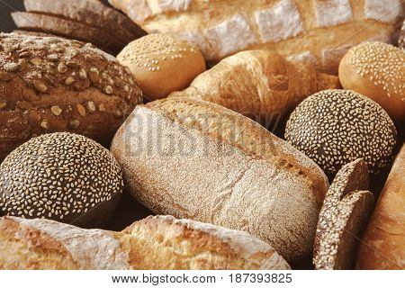 Bread background, closeup of white, black and rye loaves on black