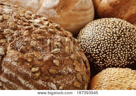 Bread background, closeup of white, black and rye bun and loaves