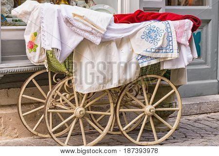 A Old fashioned baby carriage with wooden wheels