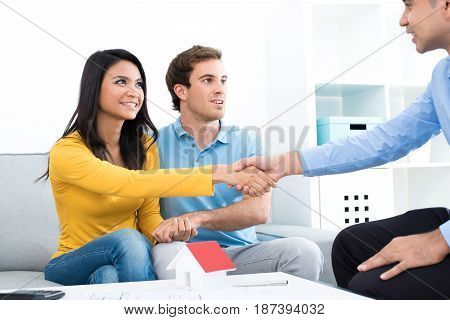 Young couple meeting with real estate agent (or financial adviser) at home