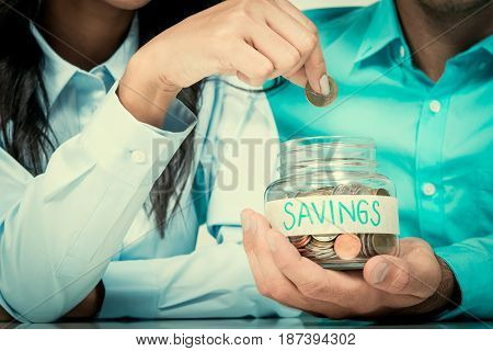 Woman hand putting money (coin) in the glass jar labeled SAVINGS held by a man