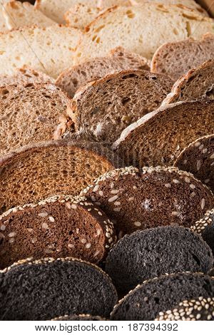 Sliced black bread gradient background. Bakery and grocery concept. Fresh, healthy whole grain sliced sorts of rye and white loaves on wood