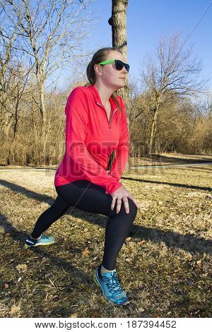 A woman stretches her legs before a morning jog in the park