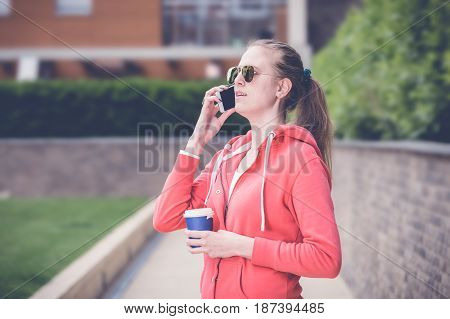 Young urban woman holding and speaking on the smartphone. She is holding paper cup of coffee.