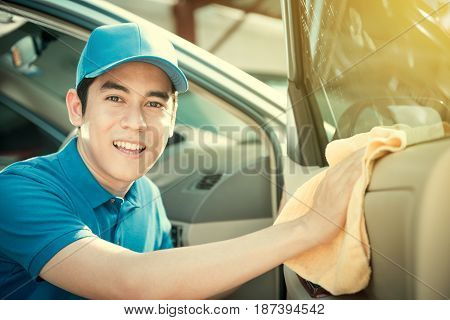 Smiling auto service staff cleaning car door - car detailing and valeting concept