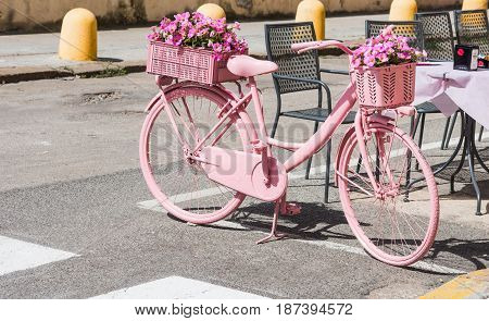 Alghero Italy - May 05 2017: Pink bike with flowers parked on the street
