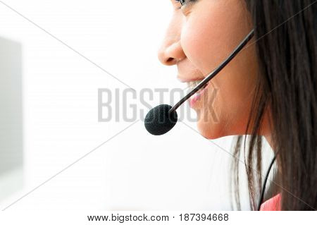 Woman wearing microphone headset - call center and customer service concepts