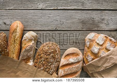 Bread border on rustic wood with copy space background. Brown and white whole grain loaves still life composition with wheat flour sprinkled around.