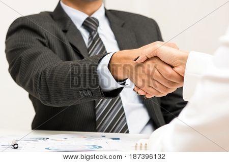 Businessman making handshake with a businesswoman in the meeting