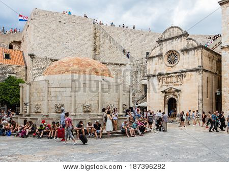 DUBROVNIK CROATIA - JULY 16th 2016: Stradun street starting square in Old Town with the Renaissance architecture of Saint Saviour church and Onofrio's Fountain under a Croatian flag atop city walls.