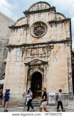 DUBROVNIK CROATIA - JULY 16th 2016: tourists passing by Saint Saviour church's front gate and façade of Renaissance architecture at Stradun street starting square in the Old Town.