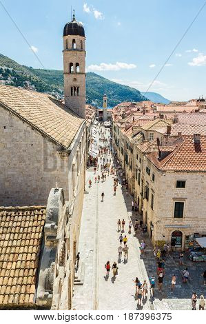DUBROVNIK CROATIA - JULY 16th 2016: tourists roaming Stradun street (the Placa) from Pile Gate to Clock Tower and beside the Franciscan Church and Monastery in the Old Town in a sunny summer day.