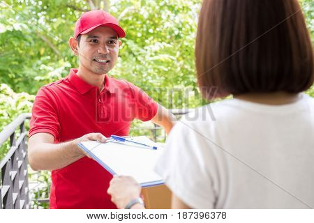 Delivery man giving clipboard to a woman to sign