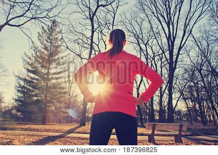 A confident woman stands with her hands on her hips as she prepares for a morning jog in the park