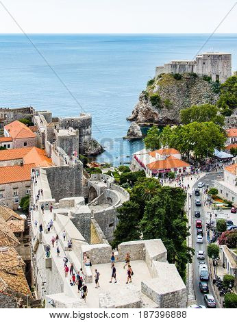 DUBROVNIK CROATIA - JULY 19th 2016: city walls and Fort Lovrijenac guarding Pile Gate entrance at Old Town. This clear waters and rocky sea cove opens to a calm and blue Mediterranean sea.