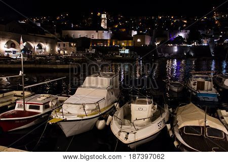 DUBROVNIK CROATIA - JULY 19 2016: night shot of leisure and fishing boats docked at Old Town's Old Port illuminated stone buildings. The former Arsenal now houses a restaurant for tourists.