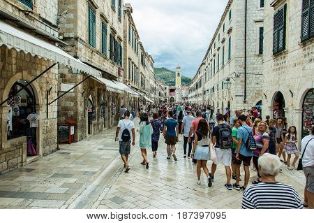 DUBROVNIK CROATIA - JULY 16th 2016: tourist crowded Stradun street (Placa) from Pile Gate to Clock Tower in the Old Town under grey clouds in a summer day.