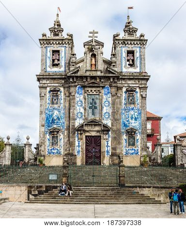 PORTO PORTUGAL - MARCH 11 2017: Saint Ildefonso church tiled facade and staircase at city old town with tourists roaming by. The painted enameled azulejos are an element of Portuguese culture.