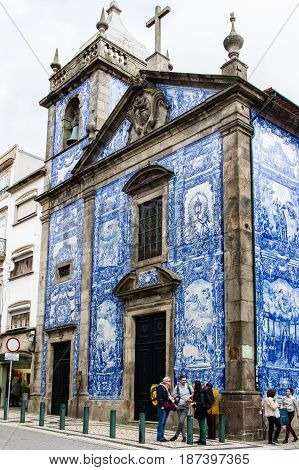 PORTO PORTUGAL - MARCH 11 2017: Chapel of Souls (Capela das Almas) church tiled front facade in Rua St. Catarina at city old town. The painted enameled azulejos are an element of Portuguese culture.