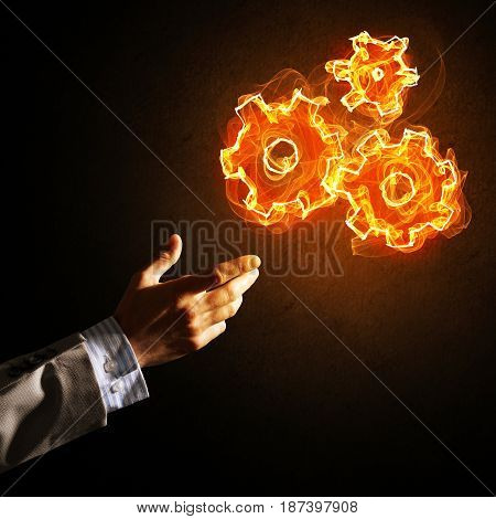 Hand of businessman pointing fire gear mechanism on dark background