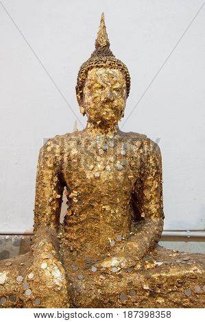 Ancient Buddha statue with the gold leaf and coin for faith in the Thai temple.(Public area not required Property Release)
