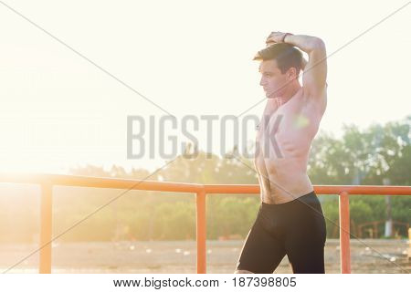 Fit man stretching his arm and shoulder warming up on fresh air