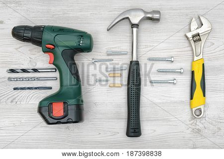 A drill, a hammer and a wrench on wooden background with nails, dowels, bits and screw bolts between them. Renovation project. Do it yourself. Building supplies.