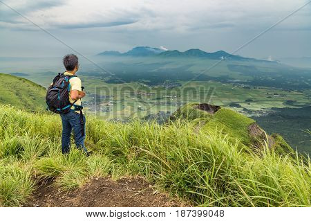hiker trekking to the hill top and watching mount Aso volcano in Kumamoto.