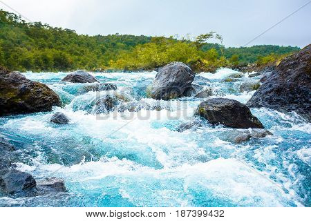 Clear blue mountain river with rocks in Chile