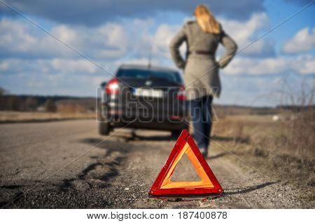 Broken car - woman driver pulled over on a country road. Warning safety triangle. Problem on the road.