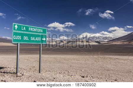 green road sign near highest chilean snow-covered volcano ojos del salado in chile