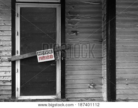 Boarded up house with Foreclosed notice on door