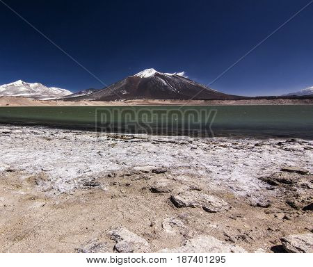 laguna verde and salty surface with snow-covered peak on background in atacama desert in chile with vlue sky