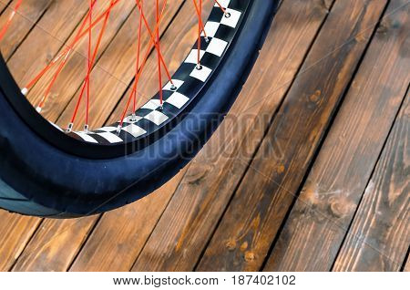 Wheel Of A Stylish Bicycle With A Black And White Rim And A Black Rubber Tire On A Stylish Wooden Ba
