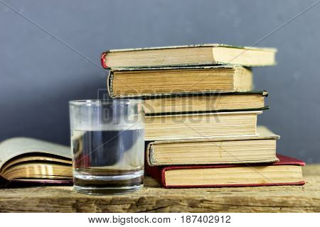 Books on an old wooden table. Glass of water.