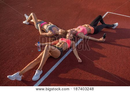 Three girls lying on the floor relaxing after training