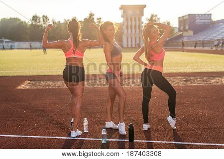Fit women on stadium showing off muscular arms flexing biceps for fun