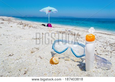 Suncream and diving mask on the sand by the sea
