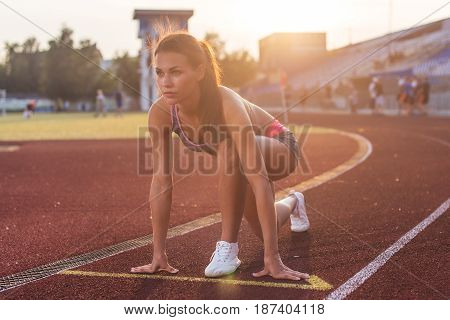 Fit woman in starting position ready for running