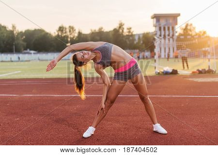 Fit woman warming up in stadium, bending and stretching her back and leg muscles.
