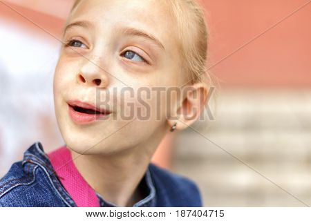Outdoor portrait of cute Caucasian blond girl near house