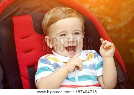 little boy sitting in a stroller. baby for a walk in a pram. child summer outdoors