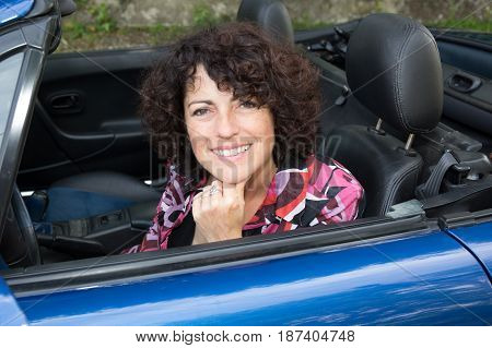 a middle-aged woman in her convertible car