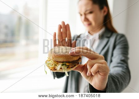 A young girl shows a sign by hand signifying there is no burger. Conceptual image of refusal from unhealthy eating. Fast food.