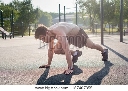 Young male athlete doing mountain climbing exercises training outside in the park.