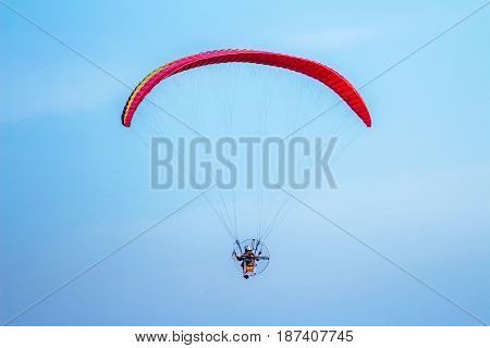 Rear view of man flying with paramotor glider parachute on beautiful blue sky