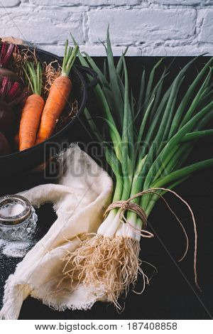Bunch of green young scallions with roots and salt on a black dark background of the old wooden boards vintage top view agriculture concept beetroot onion on cooking process on kitchen table mock up