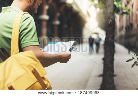 Hipster young man with backpack looking and holding map. Said view tourist traveler planning route on background sun city. Person visiting the sights Barcelona. Mockup backdrop summer street
