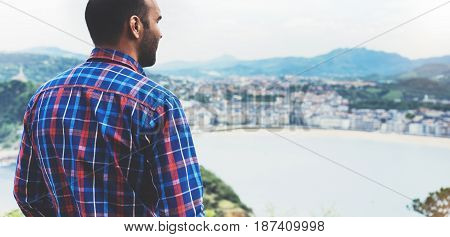 Hipster young man looking on observation deck in trip holiday in Bilbao enjoying view on seascape on mountain and ocean tourist traveler on background panoramic view of the city. Mock up for text