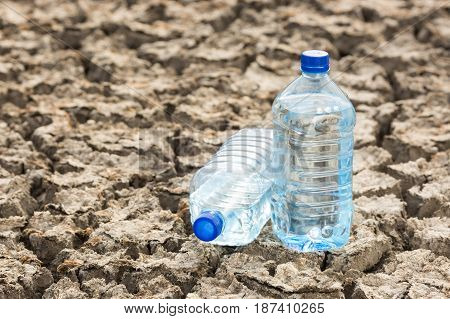 Two Blue Bottles with water on the dried soil close up. Global drought, warming, lack of water, thirst concept.